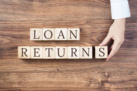 LOAN returns text on wooden blocks on rustic wooden background. Female hand holds blocks. Small business Paycheck Protection Program. Banking and finance concept, student personal or home loan return