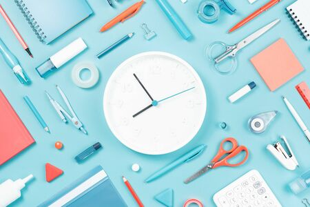 Assorted office and school white orange and blue stationery supply on pastel trendy background as knolling. White clock. Flat lay for back to school or education and craft concept.