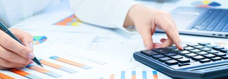 Finance and business concept. Female small business. Hand pointing at statistics chart. calculator on financial graphs on desk. Accounting budgeting loans or market analysis. finance office web banner