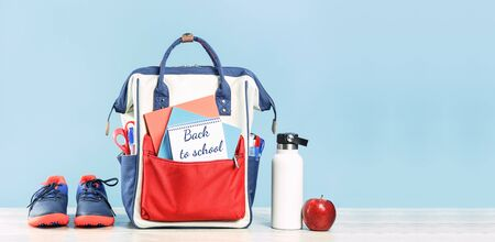 Backpack with school red and blue stationery supplies, notebooks pencils scissors with red apple water bottle on grey wooden desk. Copy space for back to school education and craft concept
