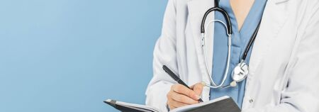 caucasian woman in doctor uniform with stethoscope writing in a notepad, Banner with copy space on blue background. Medicine and healthcare. No face 免版税图像 - 150290290