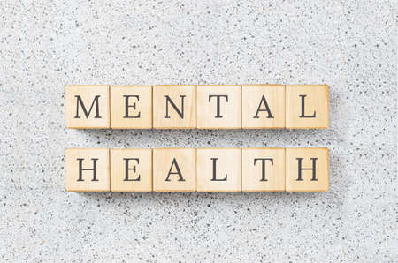 Mental health text on wooden building blocks. Minimal concept on grey cork board background. Raising awareness and mental health week and training