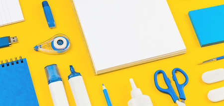 Assorted office and school white and blue stationery on bright yellow background. Organized knolling for back to school or education and craft concept. Selective focus. Banner. Copy space