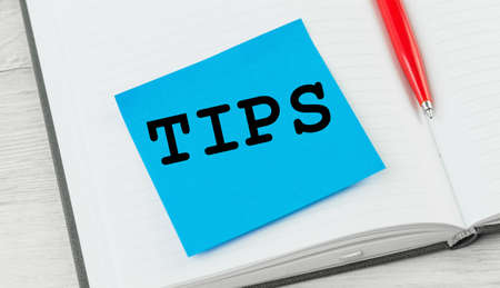 Tips word on a notebook with red pen. Top tips or quick advice concept Banco de Imagens