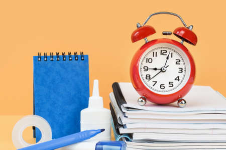 Sketchbook and note pad with office supplies and school blue stationery and red alarm clock on desk. back to school or education and craft concept. Alarm Clock at 9 oclock. Selective focus.