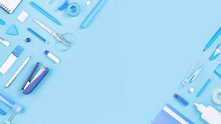 Assorted office and school white and blue stationery on pastel background as border. Flat lay knolling with copy space for back to school or education and craft concept. Blue monochrome banner