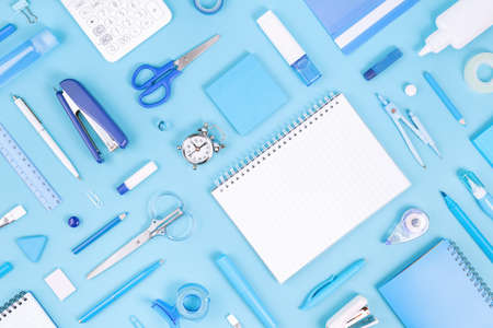 Assorted office and school white and blue stationery and notepad on pastel background. Flat lay knolling with copy space for back to school or education and craft concept. Blue monochrome banner
