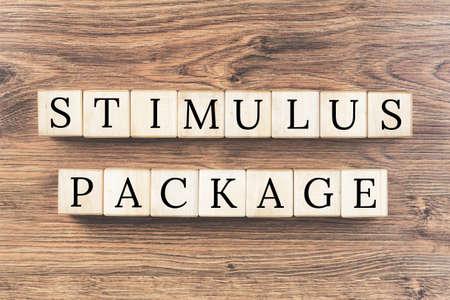 stimulus payment text on wooden blocks against textured background. Stimulus package concept Foto de archivo