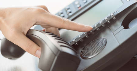 business and communications. Using voip phone in the office, close up of hand with receiver. Conference call, contact us or hotline banner. IP telephony, Telemarketing. Help desk or call centre Banque d'images