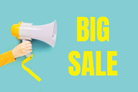 Big sale text in yellow on teal and a hand with megaphone. Sale commercial, best price guarantee. Clearance announcement. Shopping concept