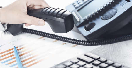business communications. Finance graphs. Using voip phone. office, close up of hand with receiver. Conference call, contact us or hotline banner. IP telephony, Telemarketing. Help desk call centre Banque d'images