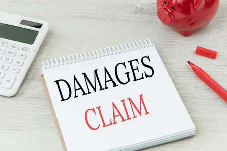 Damages claim text on notepad. Office desk with calculator and red coins bank. Business insurance, personal claim.