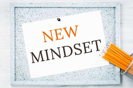 New mindset text on grey cork notice board with pencils. Flexible and innovative work approach. Success management concept