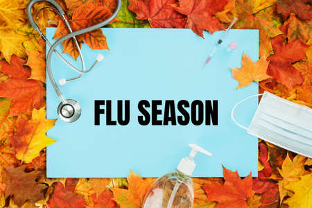 Flu season text on blue with fall leaves. Flu season or second wave. Face protective mask, sanitizer or soap and flu jab vial. Vaccine trial vaccination and immunization concept poster
