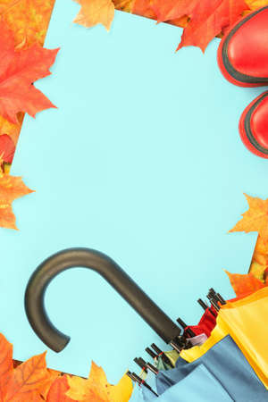 Autumn leaves frame with red rubber boots and umbrella. Fall foliage banner. Weather forecast, rain. Bright orange and red maple tree leaves. Copy space on blue