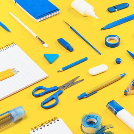 Assorted office and school white and blue stationery on bright yellow background. Organized knolling for back to school or education and craft concept. Selective focus