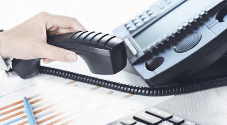 business communications. Finance graphs. Using voip phone. office, close up of hand with receiver. Conference call, contact us or hotline banner. IP telephony, Telemarketing. Help desk call centre Фото со стока