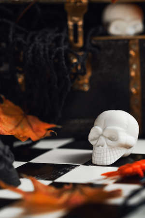 Halloween party set up props. White and black sculls with Jack O'Lantern pumpkin. Death symbol. Fear and horror concept. Dia de los Muertos and Halloween. Dark themed copy space Imagens