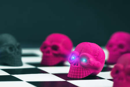 Halloween party set up props. Neon Pink and black sculls on a chess board. Glowing eyes. Death symbol. Fear and horror concept. Dia de los Muertos and Halloween. Dark themed banner