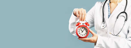 Doctors hands holding red alarm clock over blue background. Time is crutial life saver. Medical banner. Copy space. Book appointment or checkup time reminder.