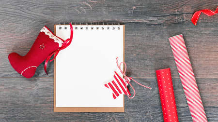 Merry Christmas mockup. Christmas stocking an open notepad on wooden background, red gift wrapping paper. New Year season greetings card resolutions mockup or goals. flat lay copy space Stock fotó