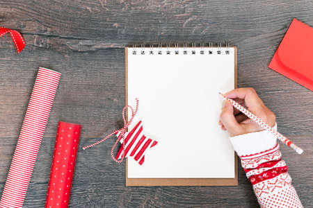Merry Christmas mockup. Hand in sweater writing in open notepad on wooden background, red gift wrapping paper. New Year season greetings card resolutions mockup or goals. flat lay copy space