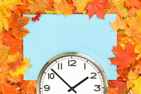 Plain wall clock in the center of autumn orange red leaves and fall foliage. Two o'clock. copy space, time management or back to school. lunch time. Opening closing hours. daylight saving time banner Stock fotó