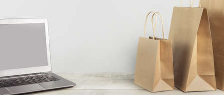 Laptop mockup with buff paper shopping carry bags on grey. online delivery service of goods and grocery, internet shopping. Environment and eco friendly packaging, plastic free takeaway. lockdown