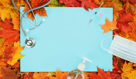 Flu and cold season frame on blue with fall leaves. Flu season or second wave. Face protective mask, sanitizer or soap and flu jab vial. Vaccine trial vaccination and immunization concept poster