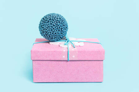 Christmas pink gift box with blue bauble on blue. Merry Christmas or Happy New Year greeting card with copy space