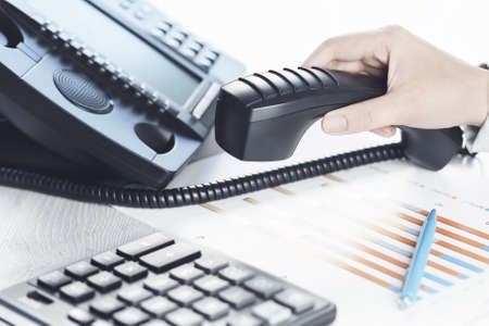 business communications. Finance graphs. Using voip phone. office, close up of hand with receiver. Conference call, contact us or financial advice. IP telephony, Telemarketing. Help desk call centre