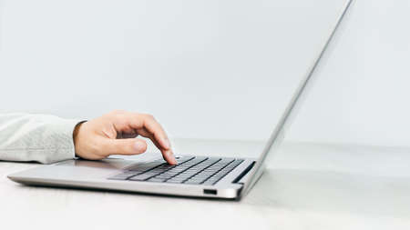 Side view of slim silver laptop on a grey desk. Female hand using the keyboard of laptop. Copy space. Minimal