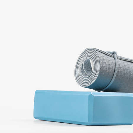 Rolled blue yoga mat and light blue foam block or brick. Gender neutral fitness and exercise concept accessories with copy space. Active lifestyle. Workout at home or gym Stock fotó