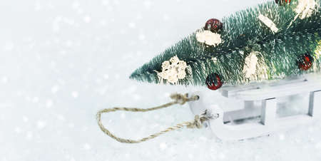 Christmas tree with toys on a sleigh on snow. Merry Christmas or Happy New Year banner card with copy space.