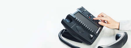 business and communications. Using voip phone in the office, close up of hand with receiver. Conference call, contact us hotline banner. IP telephony, Telemarketing. Help desk call centre. Copy space Banque d'images