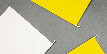 White and yellow hanging files lay flat on gray background. Banner with copy space and mockups for text. Office supplies or notice
