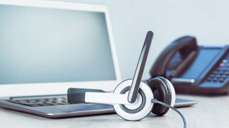 business and communications. Mockup laptop and voip phone in the office. Webinar or online conference. laptop with headset on desk. IP telephony, Cold calling. Office work or learning. Copy space
