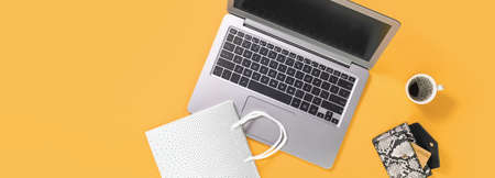 Laptop with gift shopping bags on trendy yellow orange background with coffee cup, credit card in a purse. Online internet shopping concept flat lay with copy space. Black Friday Cyber Monday Stock Photo