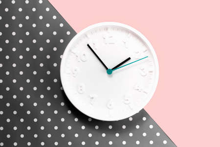 Plain wall clock in the center of polka dot brown gray and pink background. Two o'clock. Close up copy space, time management or female owned business. lunch time. Opening or closing hours. Schedule