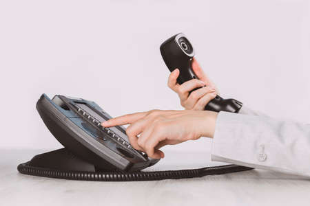 business and communications. Using voip phone in the office, close up of hand with receiver. Conference call, contact us or hotline. IP telephony, Telemarketing. Help desk or call centre