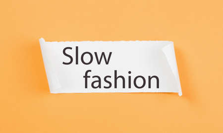 Slow Fashion text on tirn notice paper on plain yellow background. Sustainable approach to manufacturing and eco-friendly anti-consumerism concept. Conscious buying awareness. Copy space