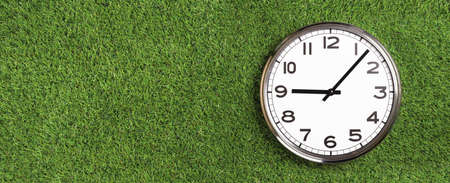 White plain analogue wall clock on green turf grass background. Five past nine oclock. copy space, game time management concept. opening or closing hours. Ecological sustainable business banner