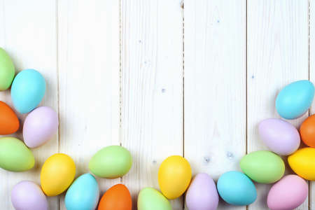 Several bright color dyed easter eggs on wooden background in flat lay with copy space. Border for Happy Easter minimal concept card or banner Banque d'images