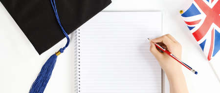 Black Graduation Cap with notebook British Union Jack flag and a hand writing in a notebook. Educataion knowledge and learning in English in Great Britain. Thesis writing with copy space banner