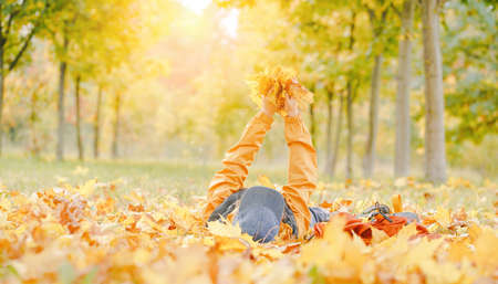 Fall. happy kid laying on the golden foliage with background of autumn trees landscape. Playing with maple leaves. Bright banner. copy space. Back to school or hello autumn