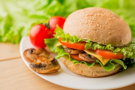 Vegetarian burger with mushrooms and fresh salad on the white plate on wooden table, close up Stock Photo
