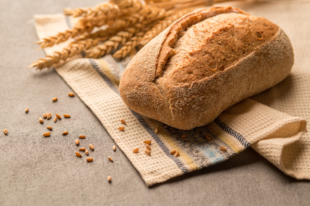 Grain healthy bread with seeds and crunchy fragrant crust is on a towel.