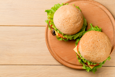 Two vegetarian burgers with fresh vegetables on rustic wooden table, top view. Healthy fast food background with copy space.