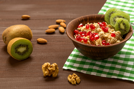 Morning healthy food, oatmeal with fruits and nuts, kiwi and pomegranate