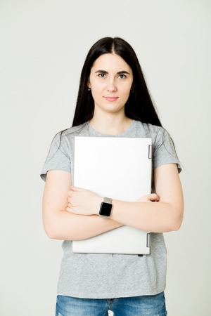 Young woman standing and holding laptop. Happy young girl with laptop, close up, freelance concept
